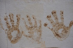 The hand stains of mud print on the cement wall. Children's hands. They play with mud and they print their hands on the wall. Naughty and creative play by children concept.