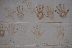 The hand stains of mud print on the cement wall. Children's hands. They play with mud and they print their hands on the wall. Naughty and creative play by children concep