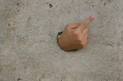 The hand that went through the concrete wall points to the corner of the wall with a finger.