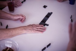 The hand that wins. Senior people playing dominoes  at home. Focus is on hands.