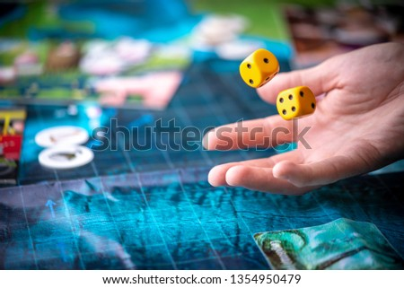 The hand throws two yellow dice on the blue playing field. Gaming moments in dynamics. Luck and excitement. Concept Board games strategy
