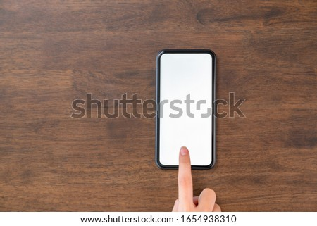 The hand touches the blank screen of the smartphone. Template for placing your ad.