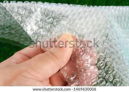 The hand touches the bubble wrap. The concept of touch, tactility, feelings.