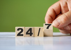 The hand turn wooden block and change word to 24/7. All day open concept background.
