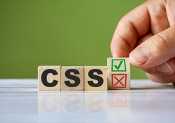The hand turn wooden block with red reject X and green confirm tick as change concept of CSS programming language. Word CSS conceptual symbol.
