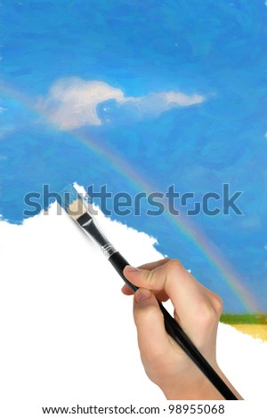 The hand with a brush draws a landscape.The blue sky, field and rainbow