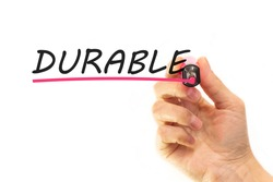 the hand writes the word durable with a marker on a white background. business concept