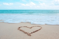 The hand writing heart shaped on the beach by the sea with white waves and blue sky background