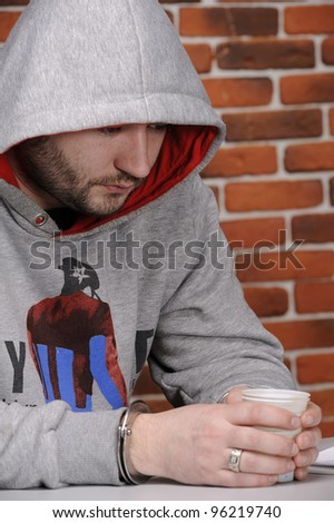 The handcuffed detainee drinks coffee against a break wall