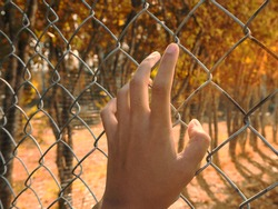 The handle on the fence represents the absence of freedom and detention.