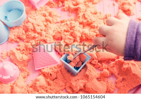 The hands of a child playing with kinetic sand.