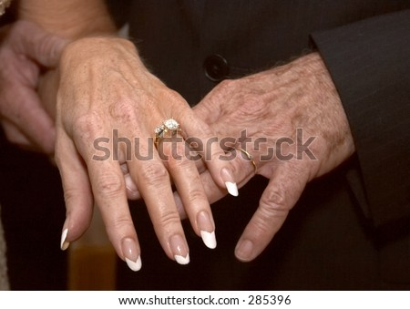 The hands of a mature, newly married couple showing off their rings (color).