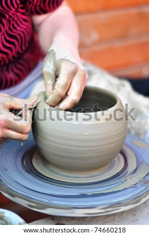 The hands of a potter creating an earthen jar