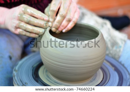 The hands of a potter creating an earthen jar