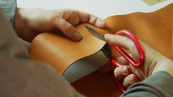 The hands of a tailor make a precise and even cut of a piece of leather with scissors for making a hand-made product for sale.
