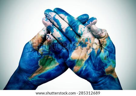 the hands of a young man put together patterned with a world map (furnished by NASA), slight vignette added