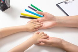 The hands of an adult are holding the baby's hands. The concept of psychological characteristics of children, the development of mental processes in children. Self-conception and psychological feature