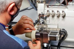 The hands of an old master set up a modern electric sewing machine and check the quality of the stitching.