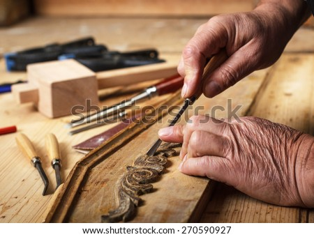The hands of an senior carpenter restoring old furniture, Close-up.