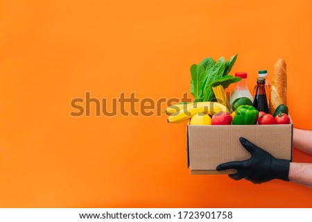 The hands of courier in protective gloves delivers box of different food on an orange background. Food delivery during virus outbreak. Safe home delivery. Takeout meal.