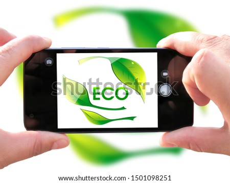 The hands of men make a telephone photograph of the flag of Ecological logo. The Concept of Ecology with Environmental Pollution from Domestic and Industrial Waste. #1501098251