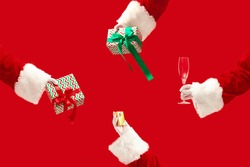 The hands of Santa Claus holding a gifts on red background with copyspace. New Year, Christmas, winter, holiday, celebration, gift concept. Giftboxes, glass for champagne and jewerly for present.