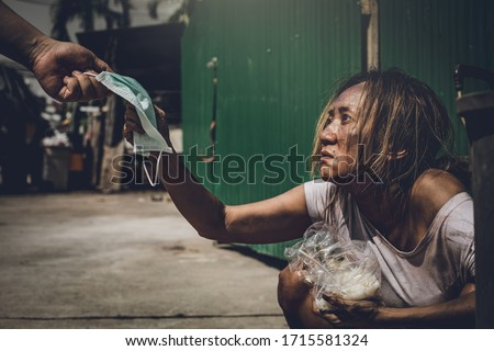 The hands of the beggars who are receiving a blue medical mask to protect the corona virus or the Covid-19. Business women who have become beggars because of the effects of the corona virus. Foto stock ©