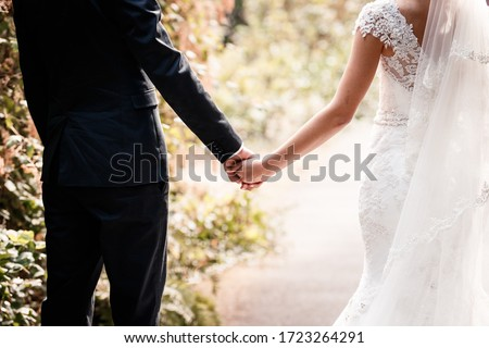Photo of  The hands of the bride and groom touch each other.Gentle touches, hugs. Wedding, celebration, ceremony