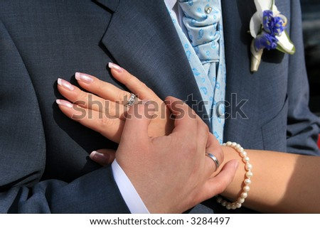 The hands of the bride and the groom near his heart