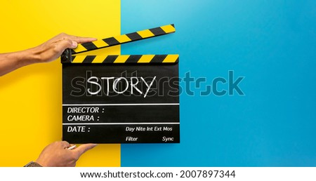 The hands of the camera crew in the film industry holding a black film slate or Clapperboard Write the word 'story' with white chalk. on a yellow and blue background Сток-фото ©