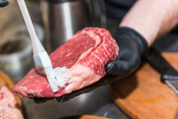 The hands of the chef lubricate raw meat