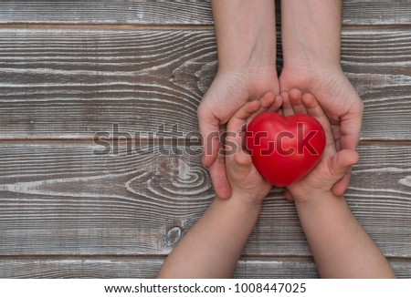 the hands of the child and the adult hold a red heart, health, insurance and family concept, the world of the day of the heart. blood donation #1008447025