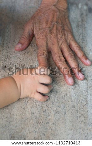 The hands of the elderly with the hands of children touching.