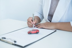 The hands of the real estate agent draw up an agreement, contractual documents on car loans.
