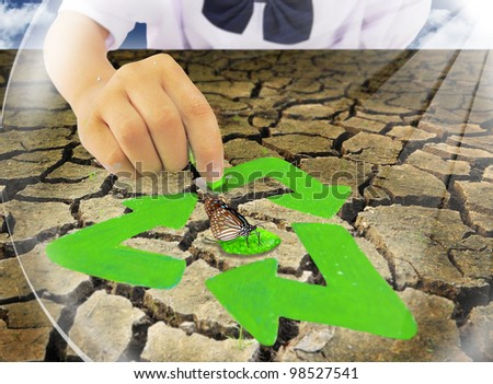 The hands of the students are painting the recycling symbol. - stock photo