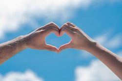 The hands of women and men in the form of hearts with blue skies and clouds Hands in the form of love hearts - love concepts