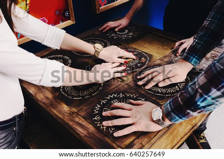 The hands of young people move pieces of the Mexican style trying to get out of the trap, escape the room game concept #640257649