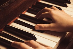 the hands on the piano keys. Photo piano in retro style.
