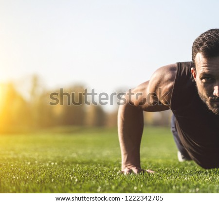 The handsome sportsman pushing up on the grass