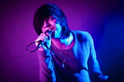 The handsome young emo guy is singing in microphone on purple and blue concert lighting.
