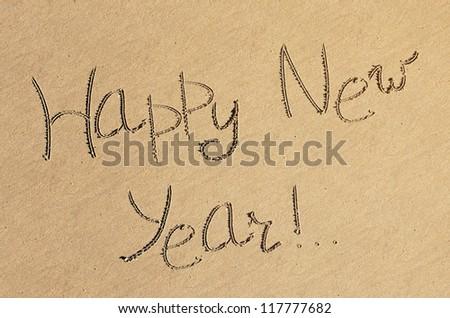 "The handwritten inscription ""Happy new year!"" on wet beach sand"