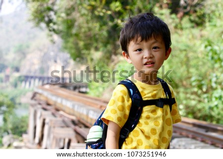 The happy asian boy (Taiwanese) visits the famous Death railway which is nearby the cliff and Kwai River in Tham Krasae, Kanchanaburi, Thailand. #1073251946