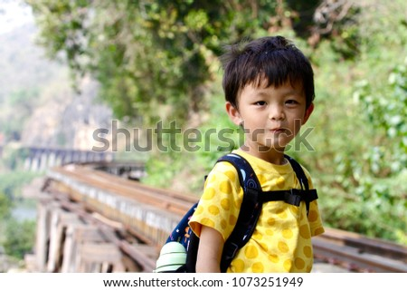 The happy asian boy (Taiwanese) visits the famous Death railway which is nearby the cliff and Kwai River in Tham Krasae, Kanchanaburi, Thailand. #1073251949