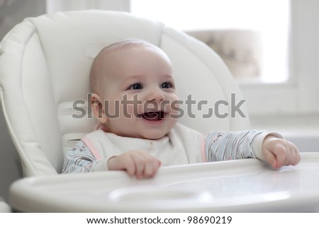 The happy baby laughing in highchair at home
