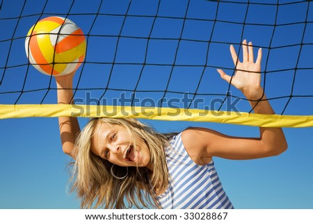 The happy cheerful girl with a ball at a volleyball net