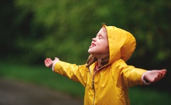 the happy child girl enjoying autumn rain