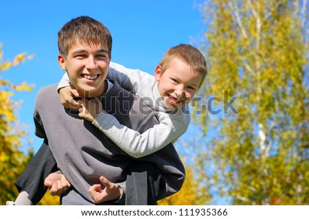 The happy child sits on the teenager shoulders