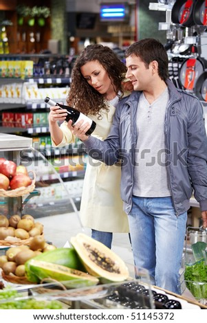 The happy couple chooses a wine bottle in shop