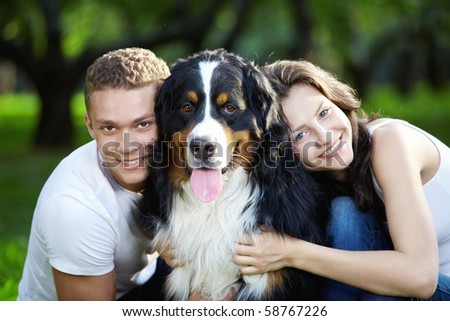 The happy couple with a dog in the park