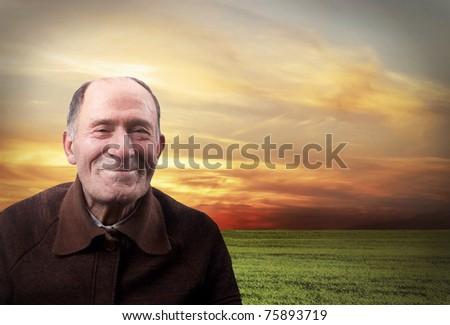 The happy elderly man against the sunset sky